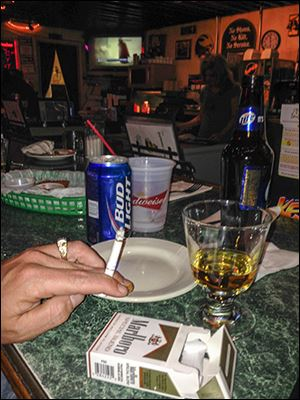 Patrons smoke at Delaney's in Toledo despite Ohio's law that bans smoking in public places. Enforcing the ordinance remains elusive for many state and county agencies since the law went into effect nearly eight years ago.