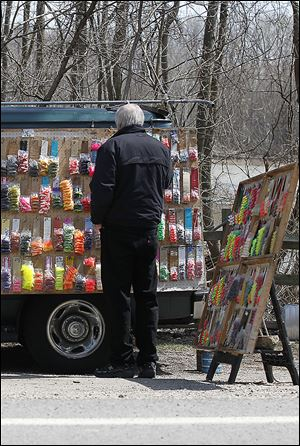 Bill McMath of Ferndale, Mich., looks over the selection of fishing lures that Clarence Labiche has for sale along the Maumee River.