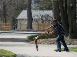 CTY rov21p   Trenton Whitlock, 10, of Toledo, flips his Razor® scooter while riding and doing tricks at the Toledo Botanical Garden in Toledo, Ohio on April 20, 2014.     The Blade/Jetta Fraser