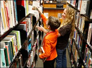 Stacey Ramirez and her son, Andres Ramirez, 11, search for books at the Bedford branch.
