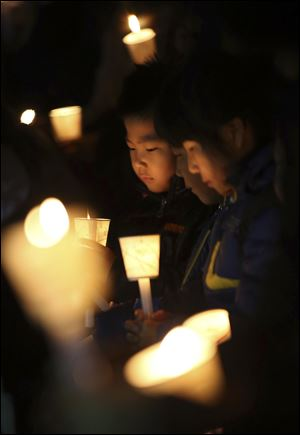 Kindergartens hold candles Sunday as they pray for safe return of passengers of the sunken ferry Sewol, in Ansan, South Korea.