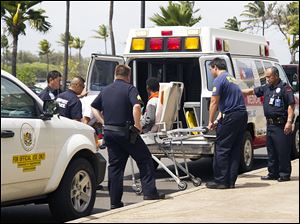 A 16-year-old boy, seen sitting on a stretcher center, who stowed away in the wheel well of a flight from San Jose, Calif., to Maui is loaded into an ambulance at Kahului Airport in Kahului, Maui, Hawaii  Sunday.