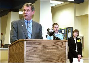 U.S. Sen. Sherrod Brown, left, talks to Perrysburg High students about student loan costs on Monday. Behind him is Owens graduate Kelly McVicker, center, and Michelle Simmons, BGSU vice p