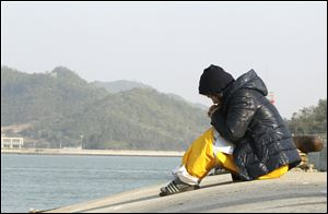 A relative of a passenger aboard the sunken ferry Sewol prays as she waits for her missing loved one today at a port in Jindo, South Korea.
