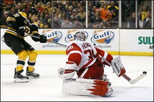 Boston Bruins' Milan Lucic, left, scores on Detroit Red Wings goalie Jimmy Howard during the second period of Game 2 in Boston.