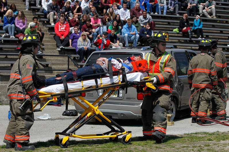 Firefighters-take-away-a-student-acting-injured-during-a-mock-car-accident