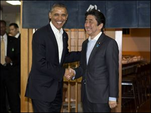 President Barack Obama and Japanese Prime Minister Shinzo Abe shake hands before having dinner at Sukiyabashi Jiro sushi restaurant in Tokyo today.