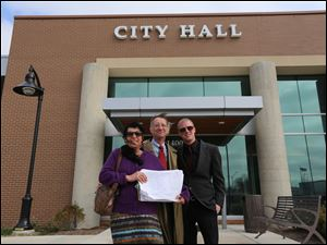 Debra Young, center, representing Safer Oak Park and Safer Hazel Park Coalition and campaign manager for Andrew Cissell, right, holds over 1,600 petitions, with Tim Beck, co-founder of the Safer Michigan coalition, at the Oak Park City Hall.