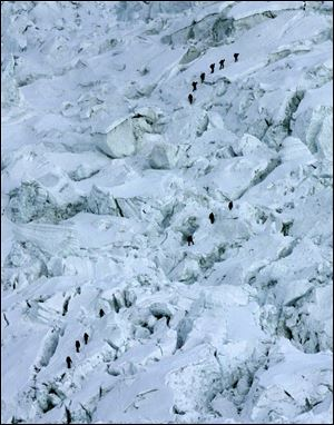 Mountaineers pass through the treacherous Khumbu Icefall on their way to Mount Everest near Everest Base camp, Nepal in May, 2003.