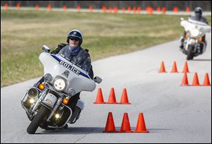 Officer Scott Swartz weaves through orange cones during the Toledo Police Department motorcycle unit's monthly training session at Owens Community College in Perrysburg Township.