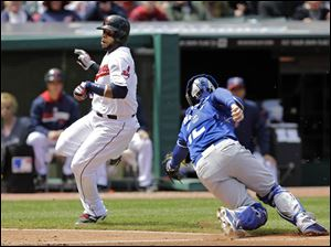 Cleveland Indians' Carlos Santana, left, avoids the tag from Kansas City Royals catcher Brett Hayes to score on a single by Michael Brantley in the fifth inning.