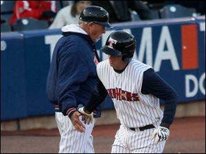 Mud Hens manager Larry Parrish greets James McCann as McCann rounds third base after hitting his first home run against Indianapolis.
