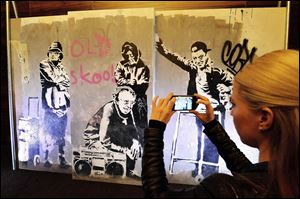 A woman photographs a section of restored wall graffiti artwork by famed street artist Banksy, as it is put on display to the public, today in London.