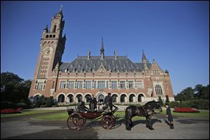 A horse-drawn carriage stands in front of the Peace Palace, seat of the International Court of Justice in The Hague, Netherlands, in August.