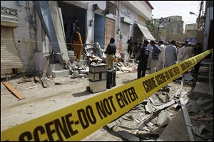 Pakistani security officials inspect the site of a bomb attack in Karachi today.