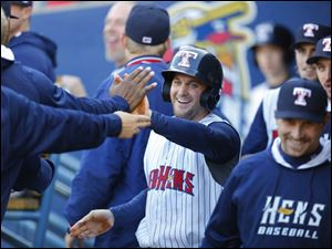 Mud Hens player Trevor Crowe is congratulated after scoring on an Indianapolis Indians error.