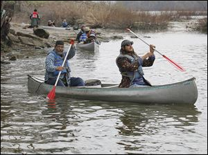 David Greene, left, and his son, Rowan, a member of Save Maumee, begin to navigate their canoe Friday down the Maumee River at Grand Rapids, Ohio. The group said 16 members were set to pad-dle the entire way from Fort Wayne, Ind., to International Park in downtown Toledo.