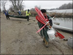 Crew medic Josh 'Turtle' Eng carries paddles as the Save Maumee group prepared to launch their boats into the Maumee River at Grand Rapids, Ohio.
