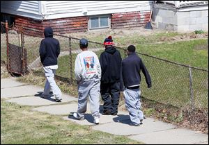 Twins Devon, center right, and Davon Lewis, back in the sweatshirt and sweatpants, walk with their friends. The brothers don't go to Soul City Boxing as often as they have in the past.