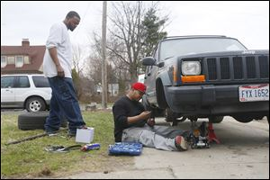 Aaron Belton, left, and his brother Chris Belton, work on fixing  Chris Belton's vehicle in front of their house. Aaron, 27, once involved with the Lil Heads gang, has pushed himself away from the streets. Chris, 25, wrote and produced the rap song 'My City.' He and his manager plan to release the album next month.