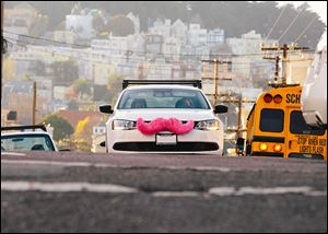 Cars of Lyft, a ride-sharing company that has come to Toledo, sport a pink mustache, the company's trademark.