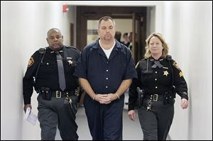 Tom Noe, flanked by Lucas County sheriff's deputies, leaves a courtroom after sentencing in this 2006 photo.