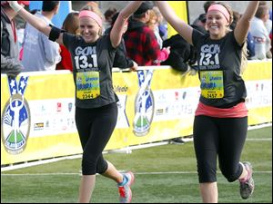 Courtney Krips, left, and Jessica Pisano, right, cross the finish line together hand-in-hand after running the half marathon during the Medical Mutual Glass City Marathon on April 27, 2014.