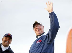 Toledo Mayor D. Michael Collins waves to the crowd at the start flanked by Toledo fire hief Luis Santiago,.