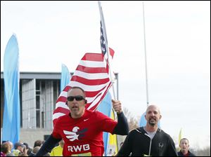 Steve Majewski crosses the finish line holding the flag after running the half marathon.