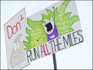 Tammy Eischen, from Toledo, holds signs as she cheers on friends who are running in the marathon.