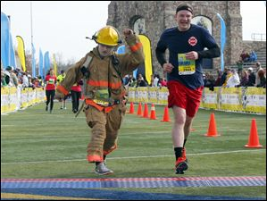 Perkins Township firefighter Matthew Riggle, left, and Willard Fire Department Dan Fial, right, finish the half marathon in honor of  fallen Toledo firefighters James Dickman and Stephen Machcinski.