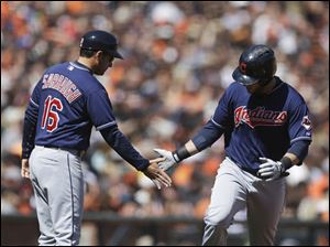 Cleveland Indians' Yan Gomes, right, is congratulated by third base coach Mike Sarbaugh after Gomes hit a home run off San Francisco Giants' Santiago Casilla in the eighth inning.