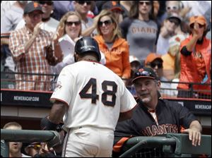 San Francisco Giants' Pablo Sandoval is congratulated by manager Bruce Bochy, right, after Sandoval scored against the Cleveland Indians in the fourth inning.