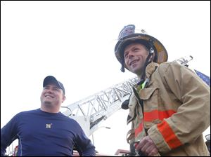 Craig Caprara, left, and Perkins Township Firefighter Brian Hackenburg, right, wait near the starting line to run the marathon. Hackenburg honored Private James Dickman and Private Stephen