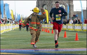 Matthew Riggle, left, Perkins Township firefighter, and Dan Fial of the Willard Fire Department finish the half marathon in honor of fallen Toledo firefighters James Dickman and Stephen Machcinski.