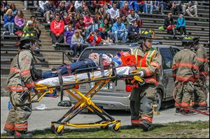 Firefighters take away an injured student during a mock-car accident at Rossford High School. Last week's grisly exercise at the stadium aimed to teach young people the dangers of driving impaired.