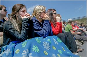 McKenna Keaton, left, Lyndsey Skala, and Kaylee Fryman watch their friends participate in the mock car accident at Rossford High School.