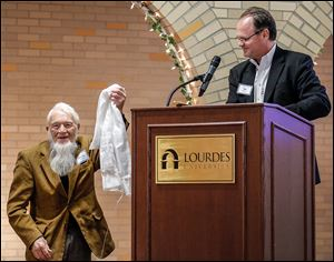 Tom Williams of Louisville presents Woody Trautman, left, a Khata blessed by the Dalai Lama during the MultiFaith Banquet Sunday at the Franciscan Center at Lourdes University in Sylvania.