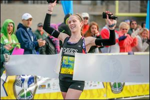 Tamara Marquardt, a Northview graduate who now lives in Shaker Heights, Ohio, crosses the finish line inside the University of Toledo's Glass Bowl to capture the women's half marathon.
