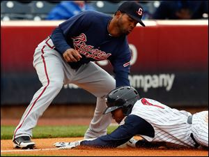 Toledo Mud Hens RF Ezequiel Carrera steals third base against Gwinnett's Edward Salcedo during the first inning.