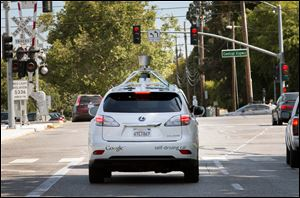 A Google self-driving vehicle navigates a street in Mountain View, Calif. Google's retrofitted Lexus RX450H sport utility vehicles have a small tower on their roofs that uses lasers to map the surrounding area. Automakers want to hide that technology in a vehicle's existing shape.