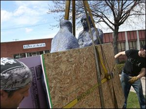 Alan Knaggs, left, and Ian Thompson, right, guide a large ceramic statue into place at its new residence.