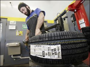 Lonn Schubert installs a Goodyear tire on a rim in South Euclid, Ohio, in February.