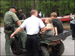 Rescue personnel attend to Dakota Kimbler, 10 and his sister Jade Kimbler, 6, after they were lost with their father inside Congaree National Park.