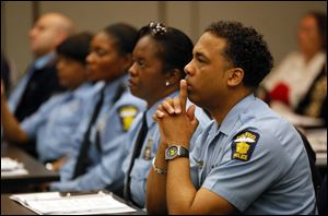 "Donald Hatch, with the Toledo Police Departmen, listens while Sgt. John Nebl of the Schaumburg, Ill., police department , not pictured, speaks during a ""Crime Free Multi-Housing Program"" event."