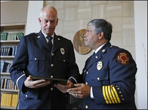 Toledo Fire Chief Luis Santiago, right, presents a plaque honoring deceased Toledo firefighter Jamie Dickman to Lt. George Simko during a University of Toledo Emergency Medicine Wall of Honor dedication ceremony today at the Radisson Hotel on the UT Health Science Campus.