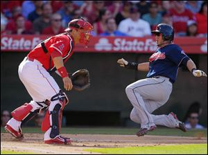 Cleveland Indians' Asdrubal Cabrera, right, scores on a single by David Murphy as Los Angeles Angels catcher Hank Conger takes a late throw.