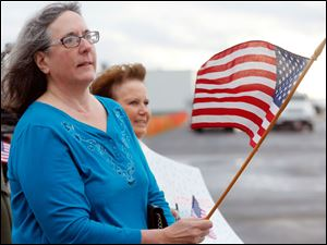 Jane Bihn, from Maumee, waves the flag and watches her father veteran Robert Bihn, not pictured, take-off.