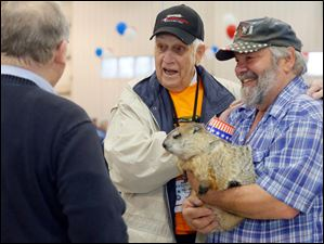Navy Veteran Harold Mucci, left, who fought in the Korean War, and Charlie Hoag, right, who is holding his woodchuck named HuckyToo, speak with well wishers before Mucci boards.