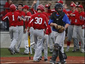 Central Catholic celebrates Richard O'Donnell's (#1) run in the 2nd inning as St. Francis catcher Drew Stark returns to his position.